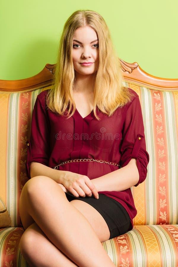 Recht junge Frau auf Weinlesesofa Art und Weise stockbilder