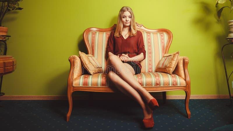 Recht junge Frau auf Weinlesesofa Art und Weise stockbild