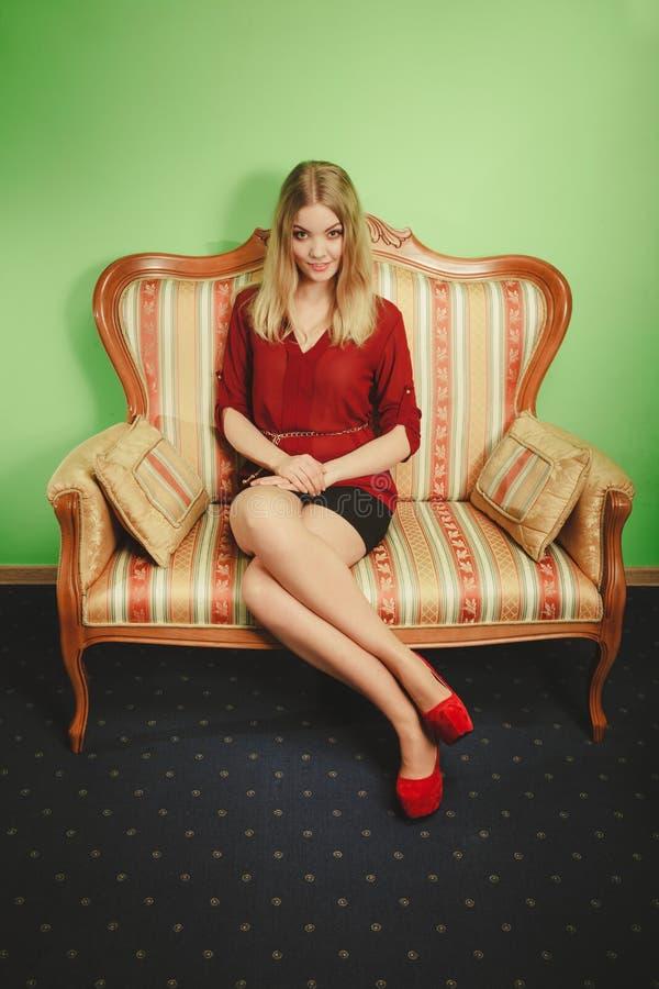 Recht junge Frau auf Weinlesesofa Art und Weise stockfotografie