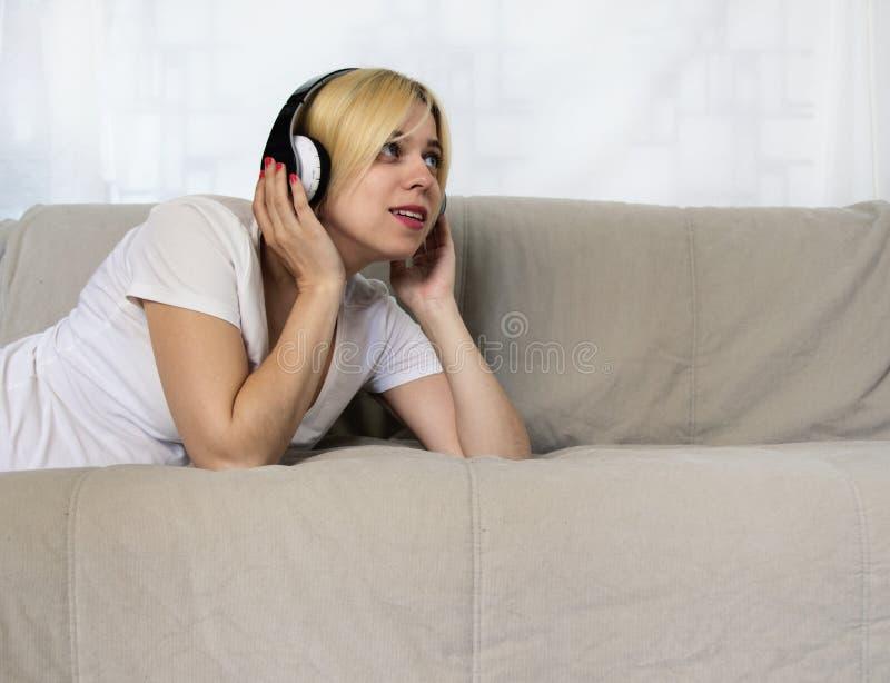 Recht junge Frau in den Kopfhörern, die auf hörender Musik des Sofas oder Audiobuch mit geschlossenen Augen liegen Frohe schöne D stockbilder