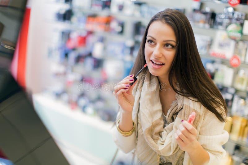 Recht junge Frau in der Parfümerie stockfotografie