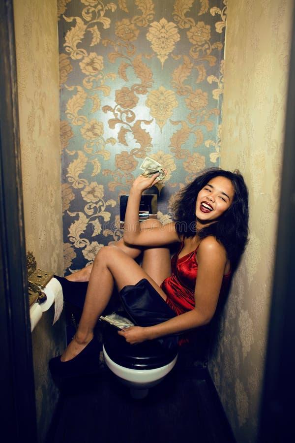 Recht junge Frau in der Toilette mit Geld, wie Prostituiertem lizenzfreies stockfoto