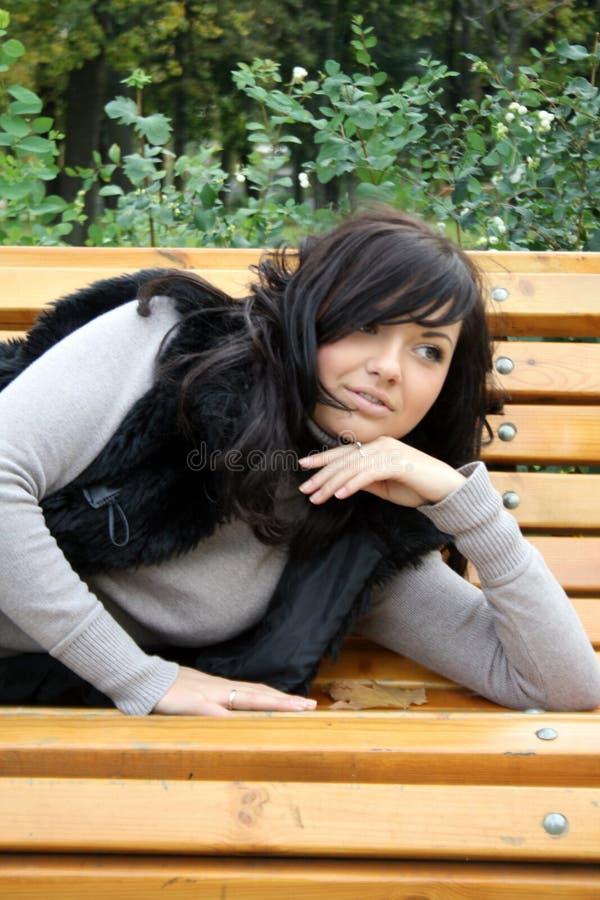 Recht junge Frau, die auf Bank liegt stockfotografie