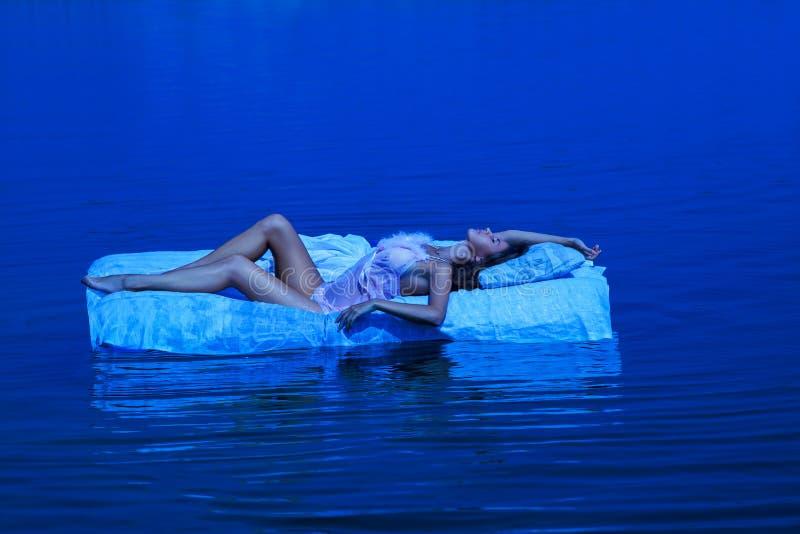 Recht junge Frau, die auf Bett im Wasser liegt lizenzfreie stockbilder