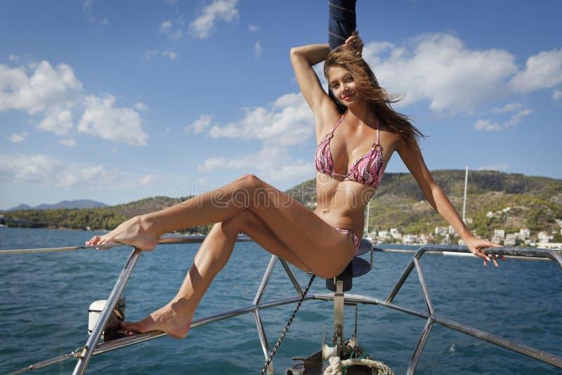 Recht junge Frau, die auf der Yacht aufwirft stockbild