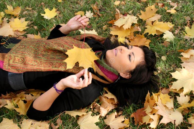 Recht junge Frau, die auf einem Teppich der Blätter liegt lizenzfreies stockbild
