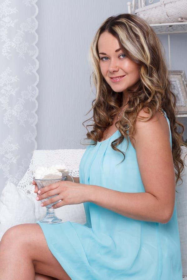 Recht junge Frau, die auf Retro- Sofacouch der Weinlese sitzt lizenzfreie stockfotos