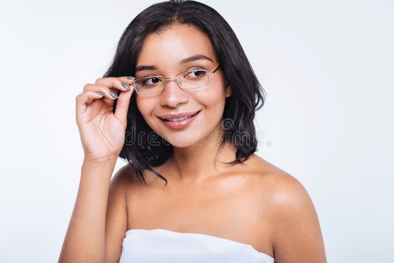 Recht junge Frau, die Brillen justiert stockfotos
