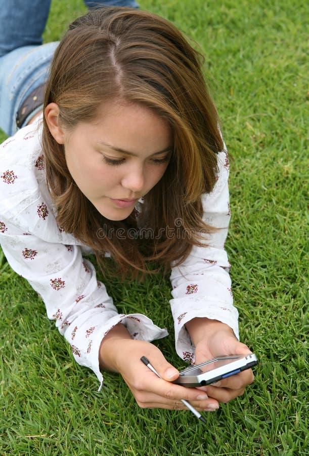 Recht junge Frau, die ein PDA verwendet stockfotos