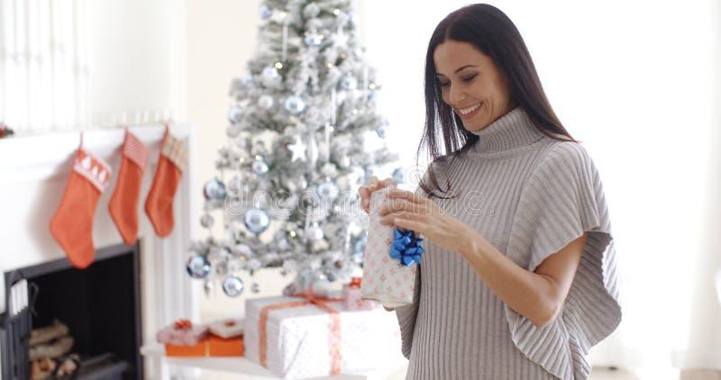 Recht junge Frau, die ein Weihnachtsgeschenk öffnet lizenzfreies stockbild