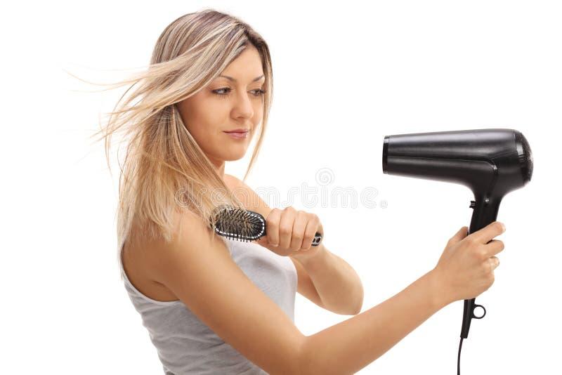 Recht junge Frau, die eine Haarbürste und ein hairdryer verwendet lizenzfreie stockbilder