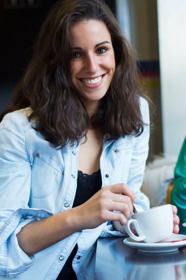 Recht junge Frau, die in einem Café mit einem Tasse Kaffee sitzt stockbilder