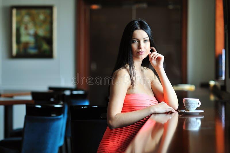 Recht junge Frau, die in einem Café mit einem Tasse Kaffee sitzt stockbild