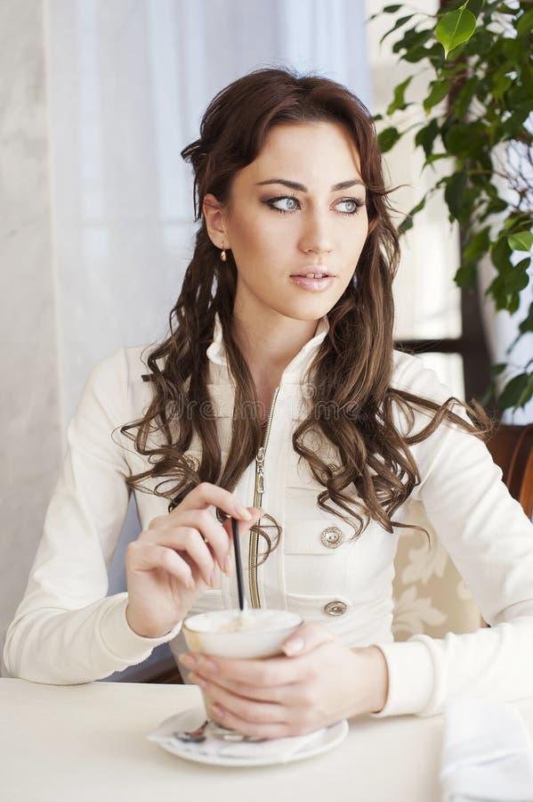 Recht junge Frau, die in einem Café mit einem Tasse Kaffee sitzt stockfoto