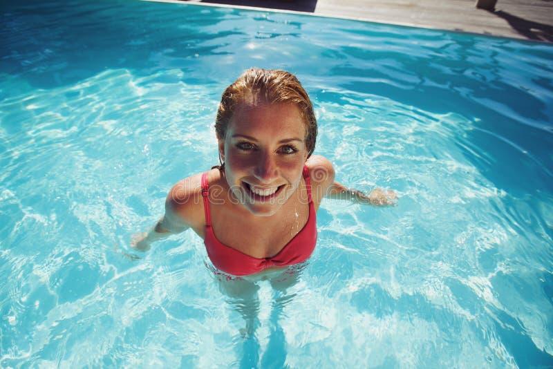 Recht junge Frau, die in einem Swimmingpool sich entspannt lizenzfreie stockfotografie
