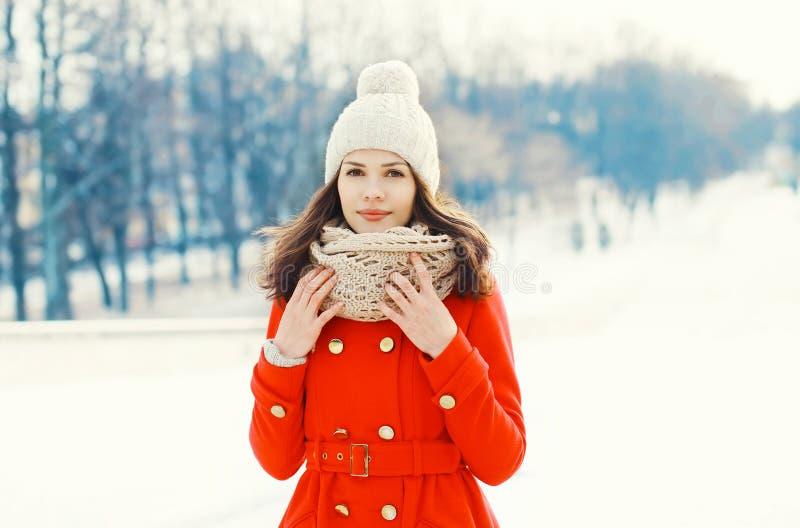 Recht junge Frau, die einen roten Mantel, eine Strickmütze und einen Schal im Winter trägt stockbilder