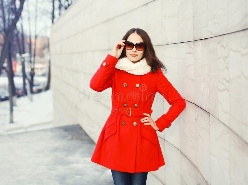 Recht junge Frau, die einen roten Mantel, Sonnenbrille und Schal trägt lizenzfreies stockbild