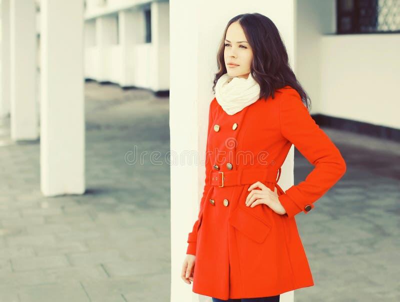 Recht junge Frau, die einen roten Mantel und einen Schal trägt lizenzfreie stockbilder