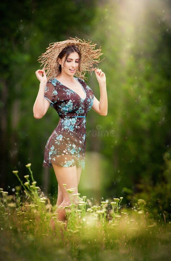 Recht junge Frau, die einen Strohhut aufwirft im Wald trägt lizenzfreie stockfotos