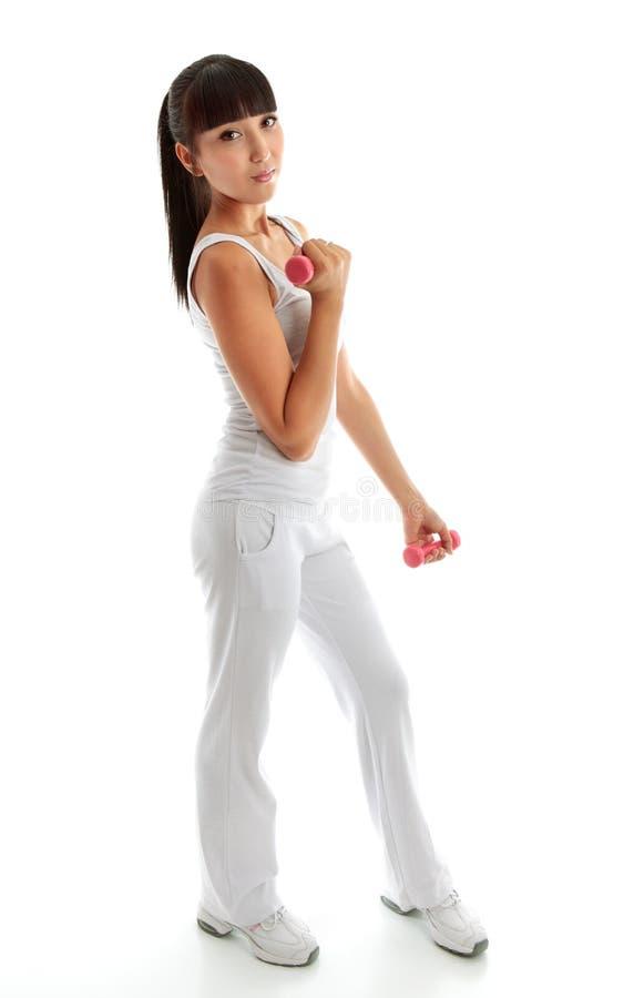 Recht junge Frau, die Gewichteignung-Training verwendet lizenzfreies stockbild