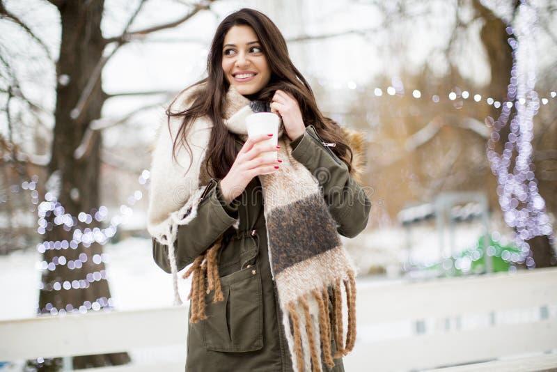Recht junge Frau, die heißen Tee an einem Wintertag trinkt lizenzfreies stockbild