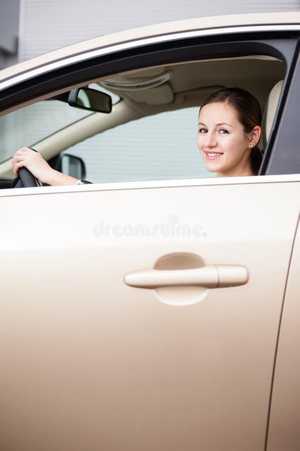 Recht junge Frau, die ihr neues Auto antreibt stockfotos