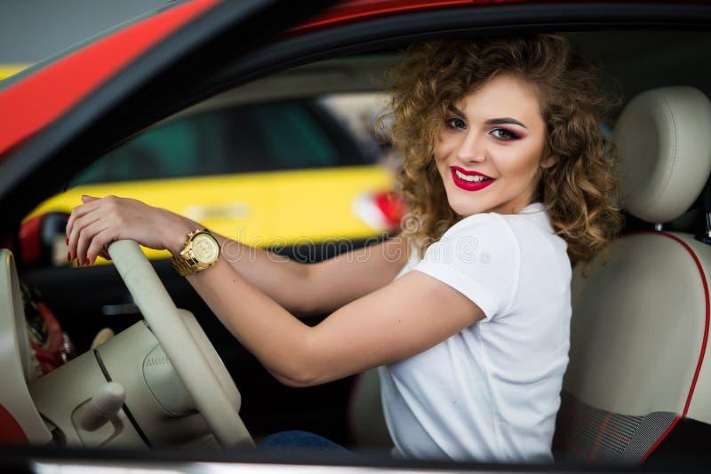 Recht junge Frau, die ihren Neuwagen und Blick an der Kamera vom Fenster fährt stockfoto