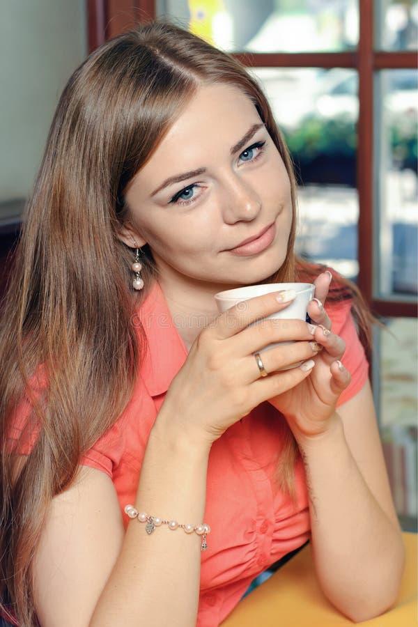 Recht junge Frau, die im Café mit einem Tasse Kaffee sitzt lizenzfreie stockfotos