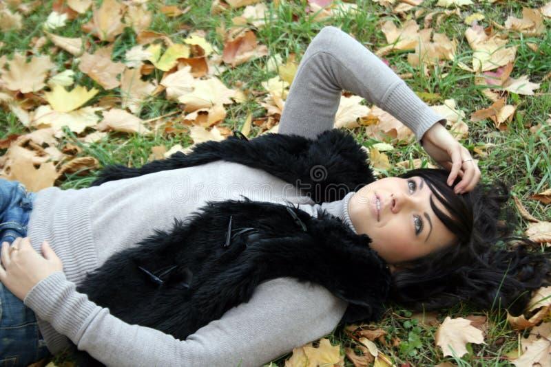 Recht junge Frau, die im Herbstpark liegt lizenzfreie stockbilder