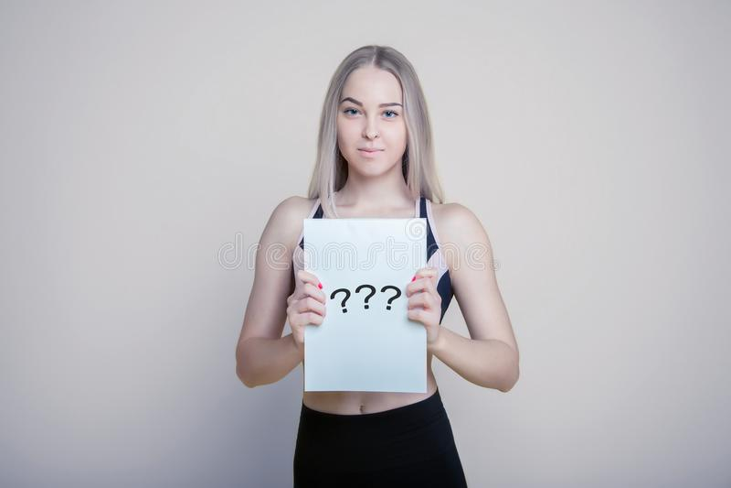 Recht junge Frau, die leeres leeres Brett lokalisiert auf dem hellen Hintergrund hält stockfotografie