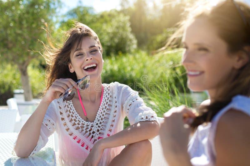 Recht junge Frau, die mit Freund am Cafétisch außerhalb des lau sitzt lizenzfreie stockfotos