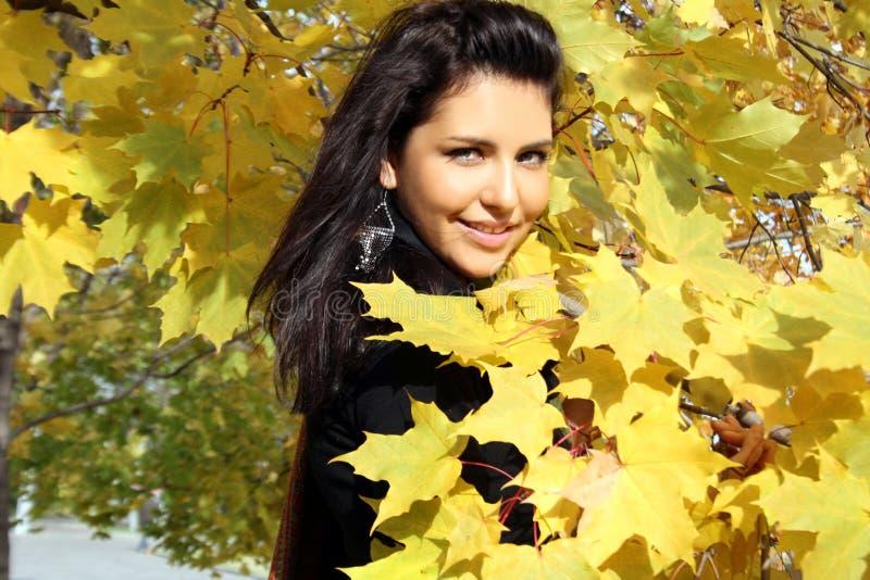 Recht junge Frau, die nahes Ahornholz steht lizenzfreies stockfoto