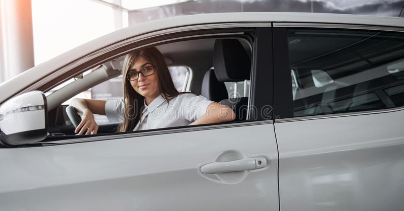 Recht junge Frau, die Neuwagen fährt stockbild