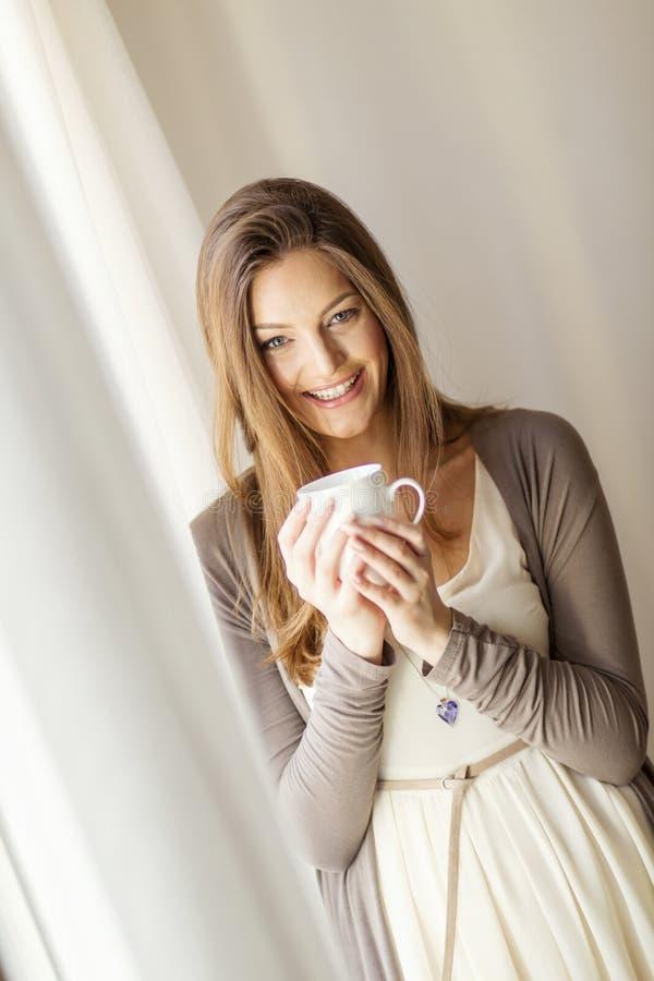 Recht junge Frau am Fenster lizenzfreies stockfoto