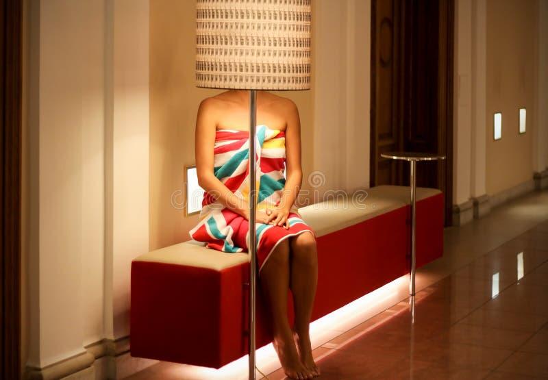 Recht junge Frau im hellen Tuch, sitzend auf der Bank stockbilder