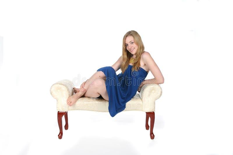 Recht junge Frau im kurzen blauen Kleid auf Bank lizenzfreie stockbilder