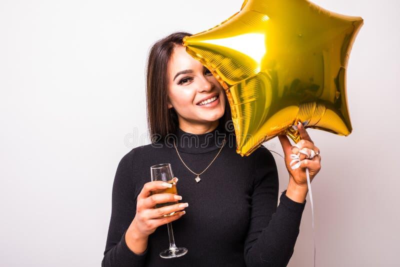Recht junge Frau im schwarzen Kleid mit lächelndem und trinkendem Champagner des Goldsternförmigem Ballons stockbilder