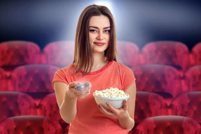 Recht junge Frau mit aufpassendem Film des Popcorns stockfotos