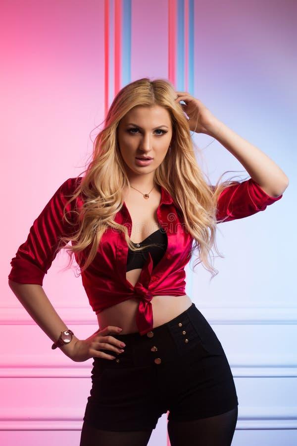 Recht junge Frau mit dem langen gewellten Haar, das am Studio in rotem s aufwirft lizenzfreie stockfotografie