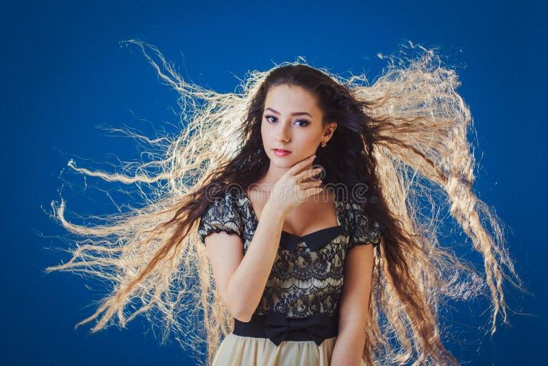 Recht junge Frau mit dem langen Haar auf blauem Hintergrund stockbilder