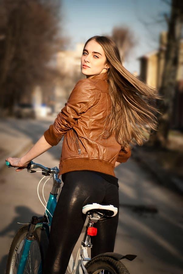 Recht junge Frau mit Fahrrad in einer Stadtstraße lizenzfreie stockfotografie
