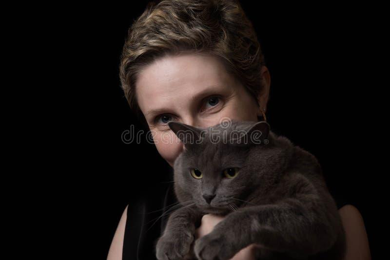 Recht junge Frau mit ihrer Katze stockbild