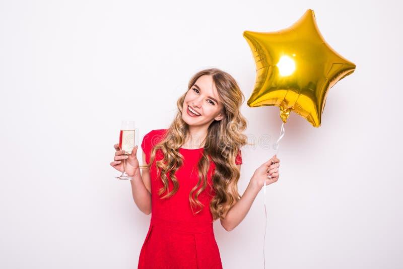 Recht junge Frau mit lächelndem und trinkendem Champagner des Goldsternförmigem Ballons lizenzfreies stockfoto