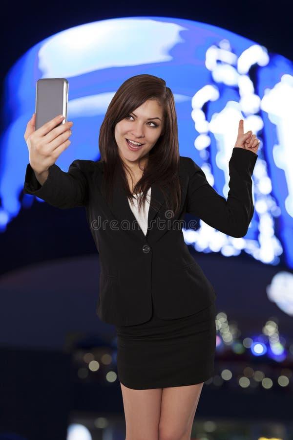 Recht junge Frau zeigt auf etwas hinten, während sie ein sel nimmt stockfotografie