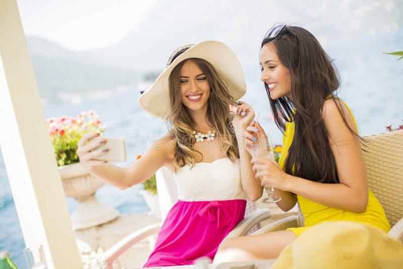 Recht junge Frauen, die im Urlaub selfie durch das Meer nehmen stockbild