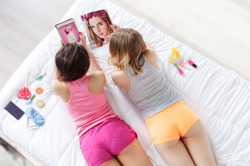 Recht junge Frauen, die Pyjamapartei machen stockfotografie
