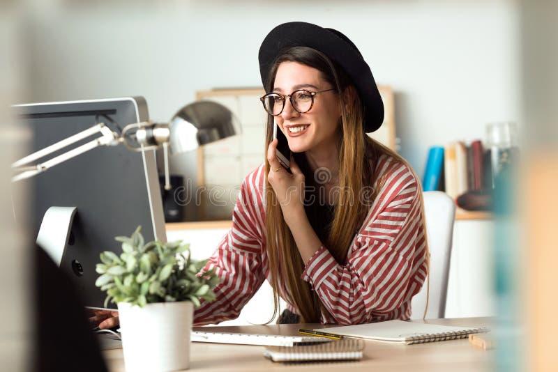 Recht junge Geschäftsfrau, die mit Laptop bei der Anwendung ihres Handys im Büro arbeitet lizenzfreie stockfotografie
