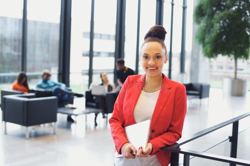 Recht junge Geschäftsfrau im Büro mit Laptop lizenzfreie stockfotos