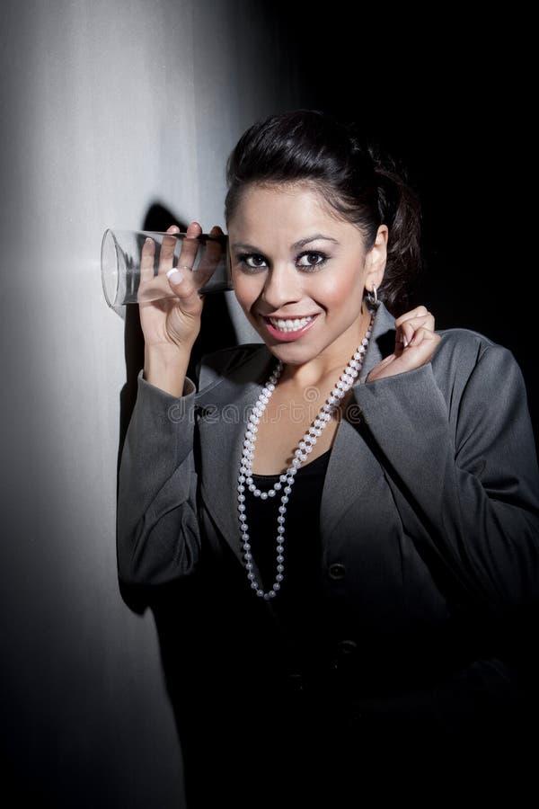 Recht junge hispanische Frau, die Glas zum eavesdr verwendet lizenzfreies stockfoto