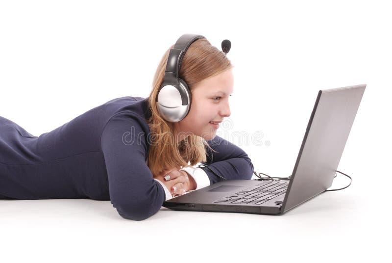 Recht junge Jugendliche mit dem Laptop und Kopfhörern, die auf dem Boden liegen stockfotografie
